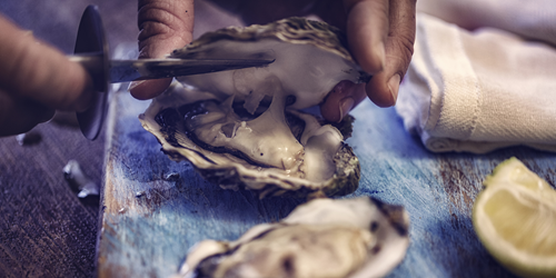 Man shucking oysters with a slice of cut lemon in the background