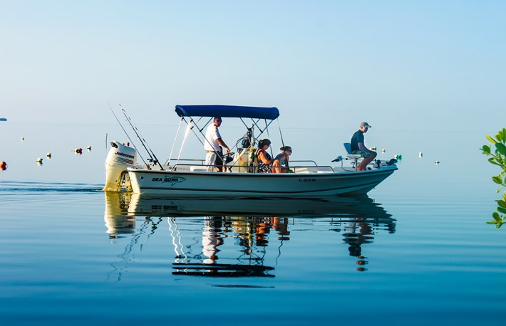 Family in fishing boat on very calm water where the ocean blends into the sky off Cudjoe Key Florida USA circa August 2010 S  By Svineyard