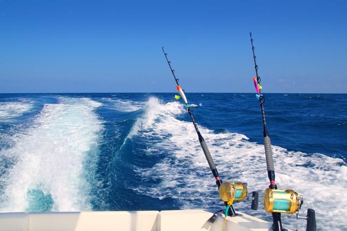 Trolling fishing boat rod and golden saltwater reels deep blue ocean sea wake
